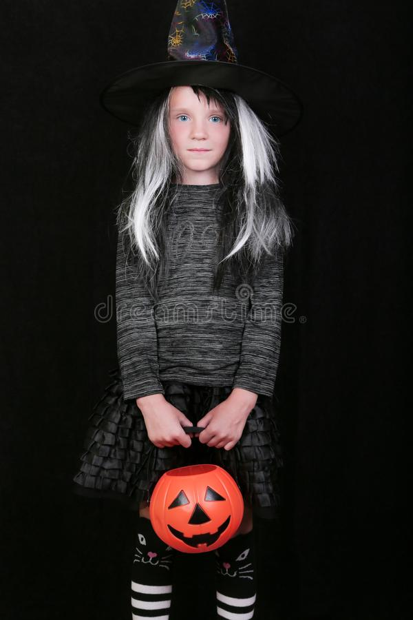 Happy laughing child girl in witch costume with Halloween pumpkin candy jar on black background.  royalty free stock photography