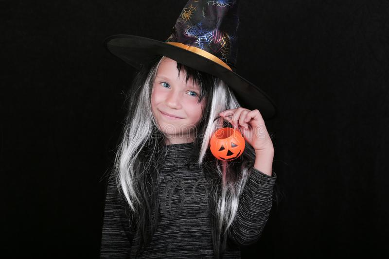 Happy laughing child girl in witch costume with Halloween pumpkin candy jar on black background.  royalty free stock photos