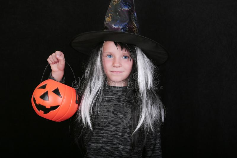 Happy laughing child girl in witch costume with Halloween pumpkin candy jar on black background.  stock image