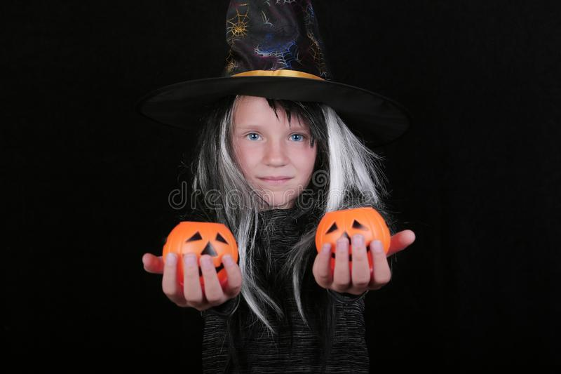 Happy laughing child girl in witch costume with Halloween pumpkin candy jar on black background.  royalty free stock photo