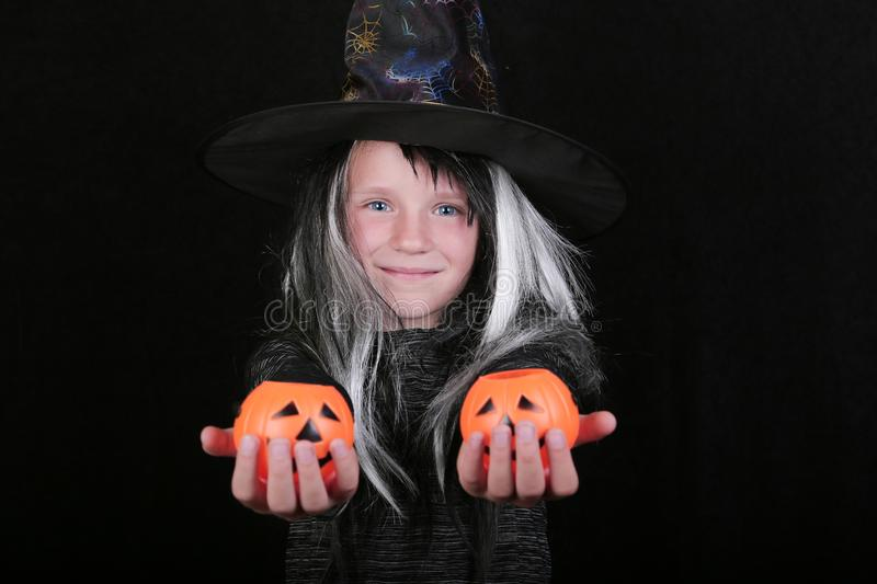 Happy laughing child girl in witch costume with Halloween pumpkin candy jar on black background.  royalty free stock image