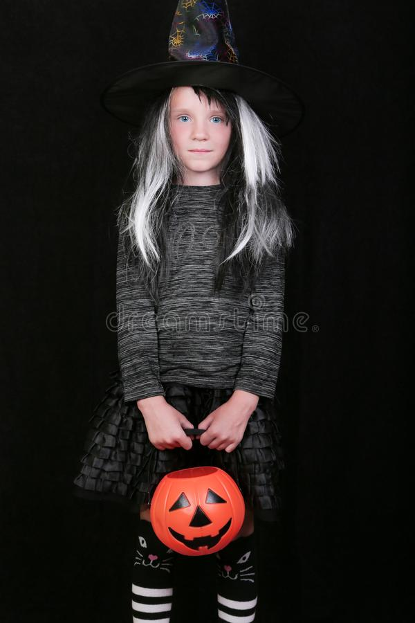 Happy laughing child girl in witch costume with Halloween pumpkin candy jar on black background.  stock images