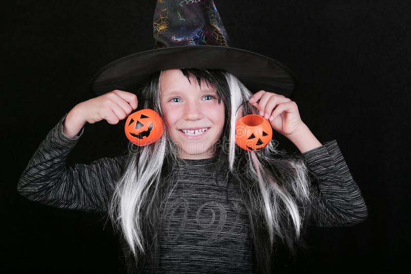 Happy laughing child girl in witch costume with Halloween pumpkin candy jar on black background.  stock photography
