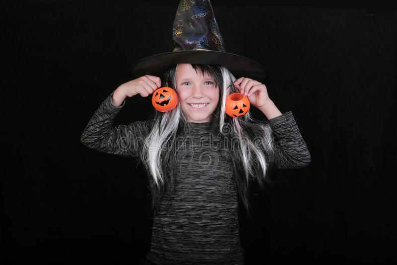 Happy laughing child girl in witch costume with Halloween pumpkin candy jar on black background.  royalty free stock images