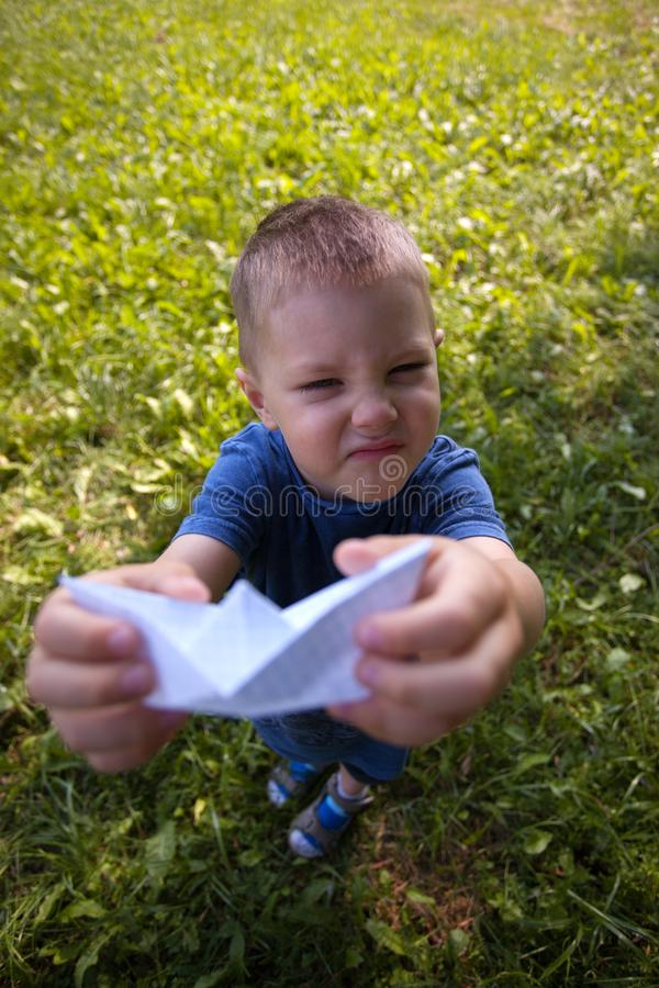 Happy laughing child hold paper ship indoors. Green field background. Happy childhood, summer, holiday, travel, vacation concept. stock photos