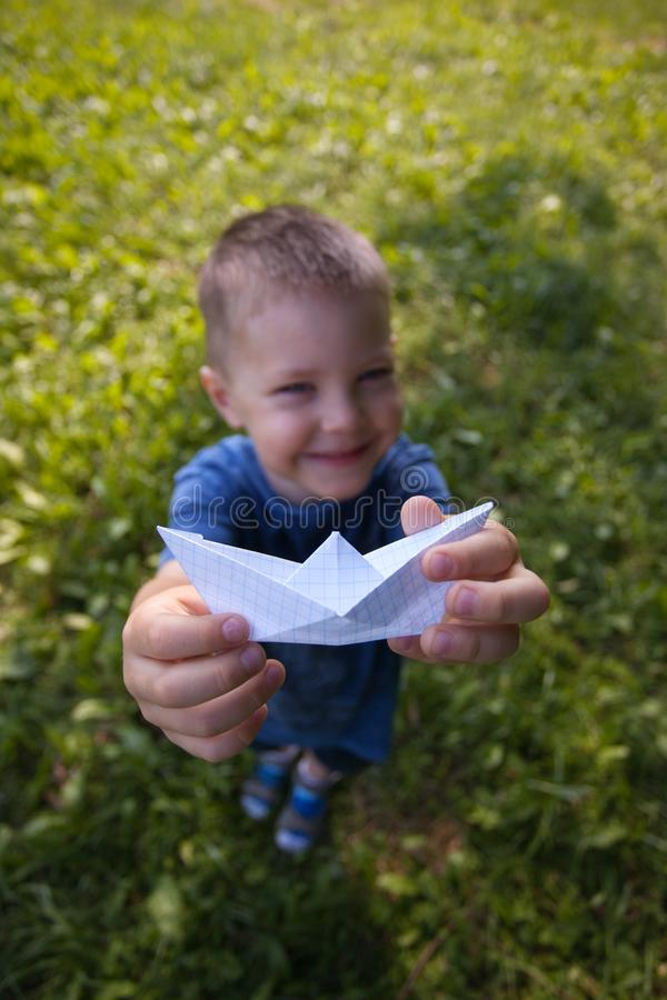 Happy laughing child hold paper ship indoors. Green field background. Happy childhood, summer, holiday, travel, vacation concept. royalty free stock photo