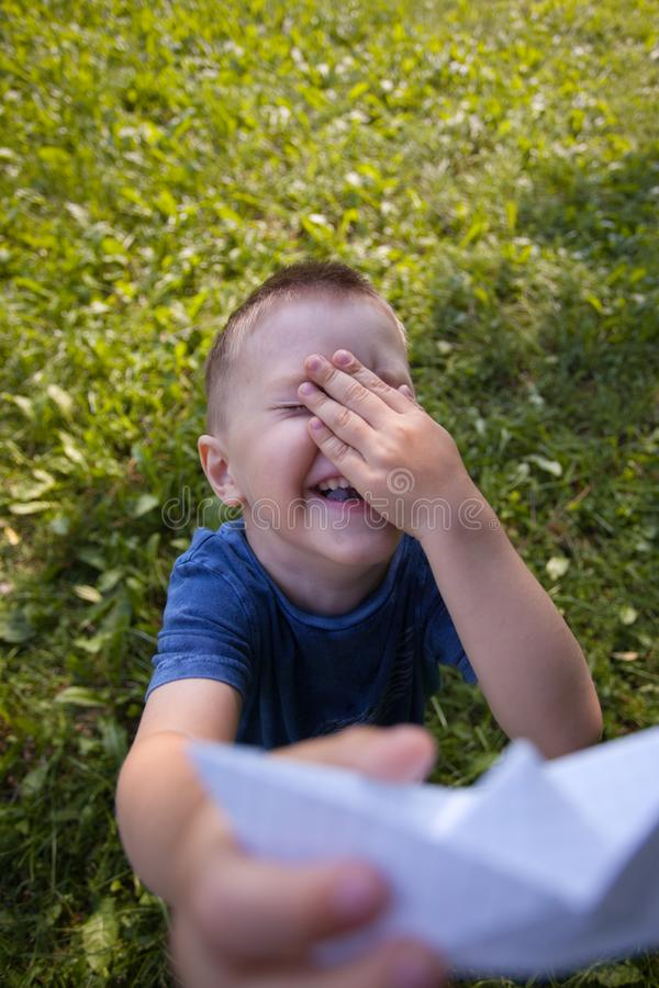 Happy laughing child hold paper ship indoors. Green field background. Happy childhood, summer, holiday, travel, vacation concept. royalty free stock image