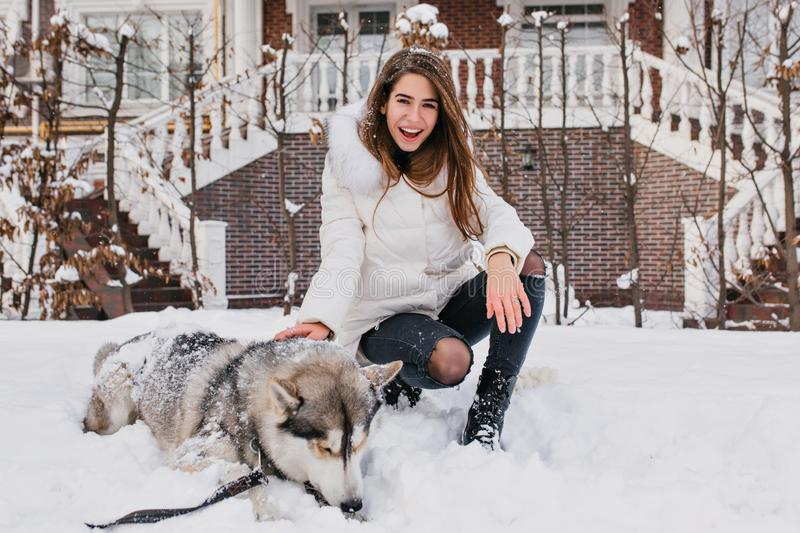 Happy laughing girl with straight hair sitting on snow beside her dog. Good-looking woman in jeans and white jacket royalty free stock image