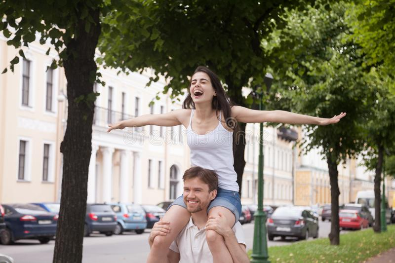 Happy laughing girlfriend sitting on boyfriend shoulders outdoor royalty free stock images
