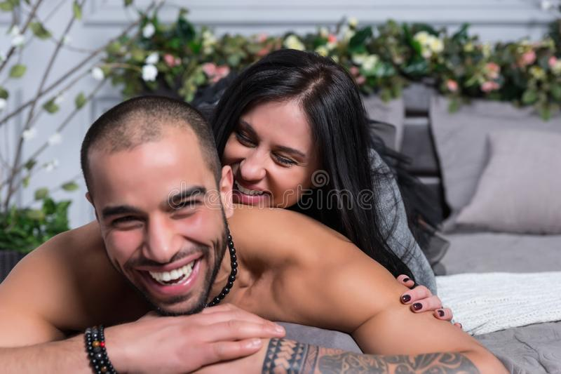 Happy laughing international couple of man with bare chest and w stock photography