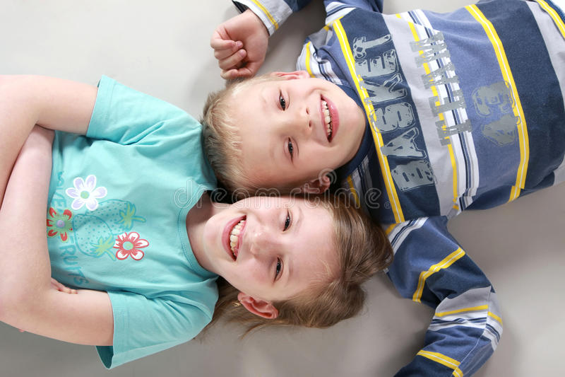 Happy laughing kids on the floor royalty free stock photos