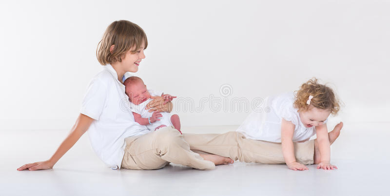 Happy laughing kids playing together in white room royalty free stock photo