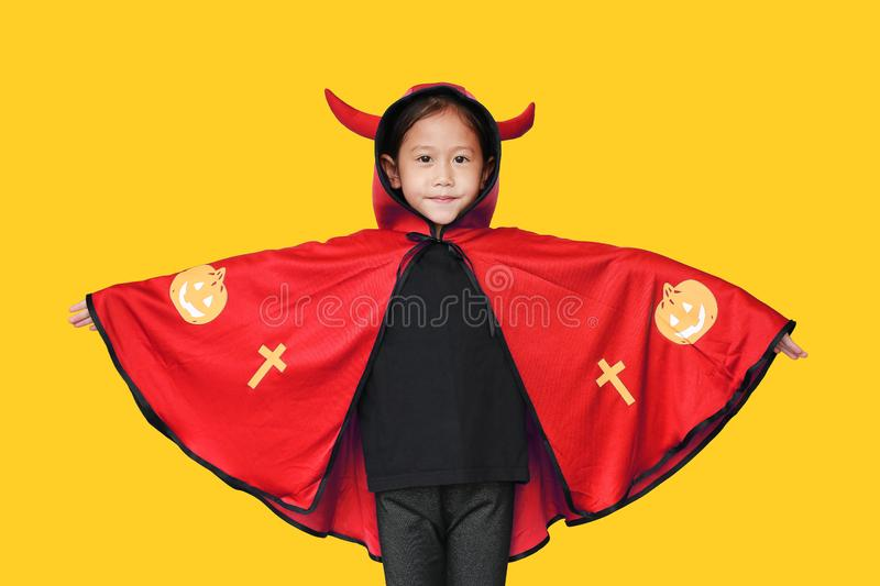 Happy laughing little Asian child girl dressed Halloween costume. Kid in Dracula robe isolated on yellow background stock images