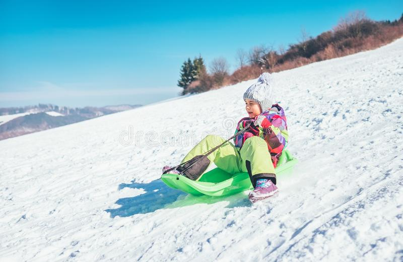 Happy laughing little girl sliding down from the snow slope. Funny winter holidays spending concept image stock photography