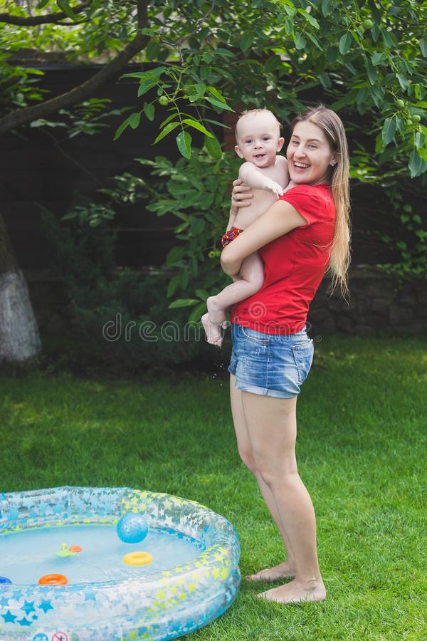 Portrait of happy laughing mother with baby boy after swimming in inflatable swimming pool royalty free stock photography