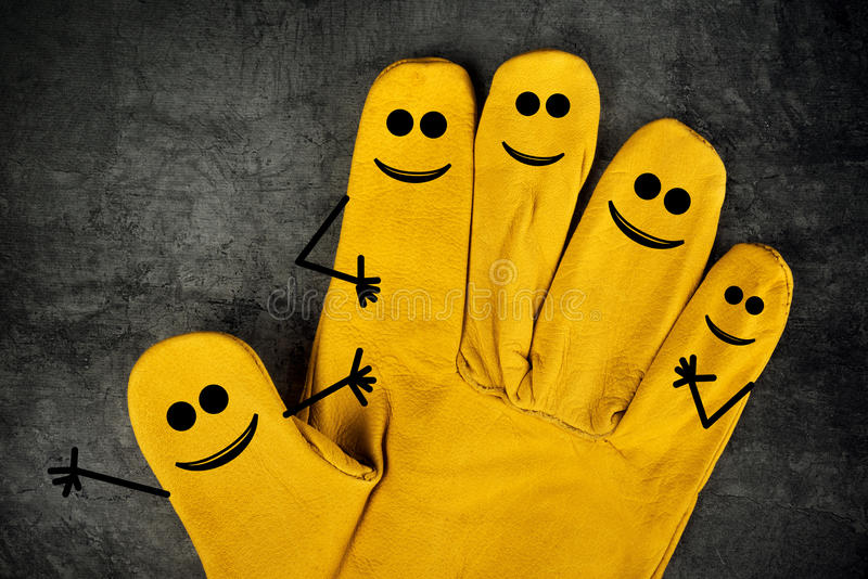 Happy Laughing Smileys on Fingers of Protective Gloves. Five Happy Laughing Smileys on Fingers of Yellow Leather Protective Construction Industry Working Gloves royalty free stock image