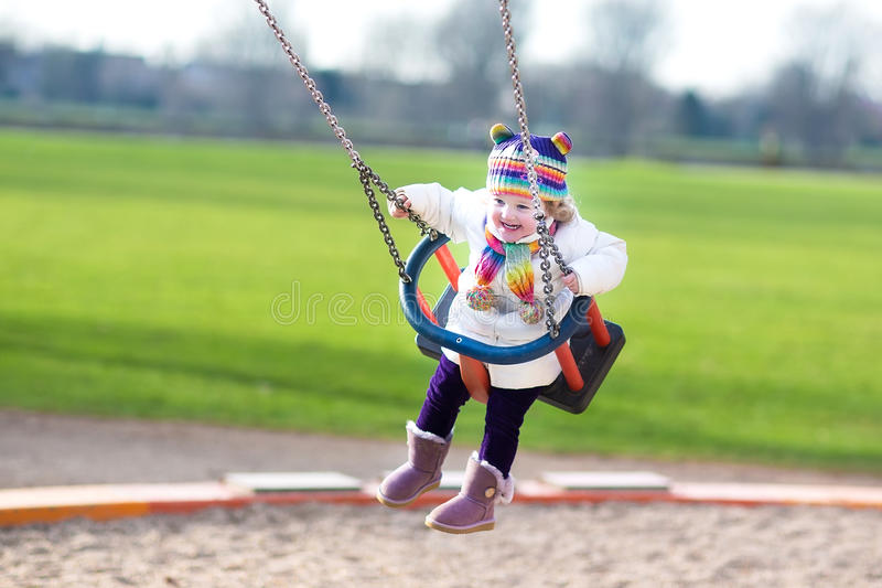 Happy laughing toddler girl swinging on playground stock images