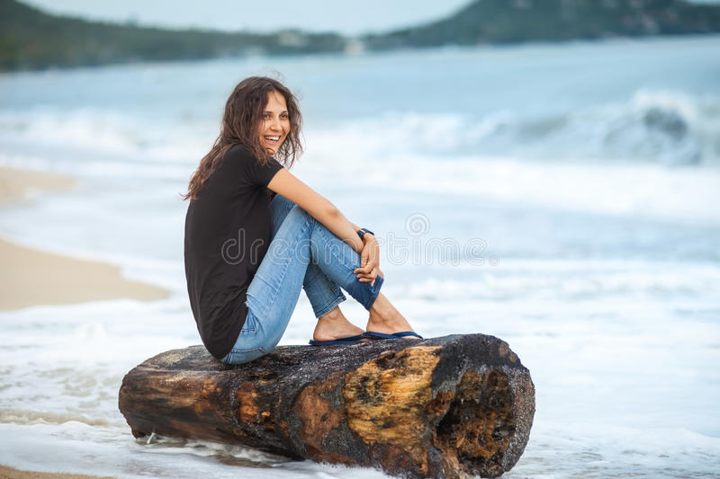 Happy laughing woman sitting on the beach royalty free stock image