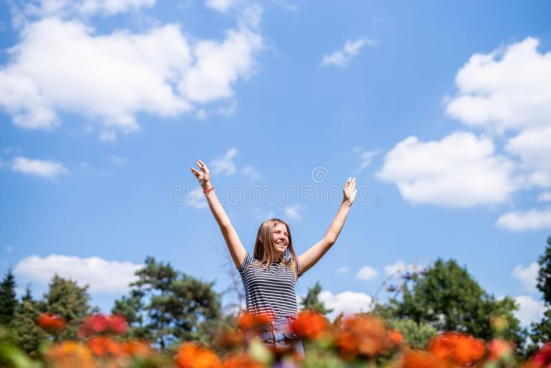 Happy laughing woman in a sunny day in nature in summer with open hands royalty free stock images