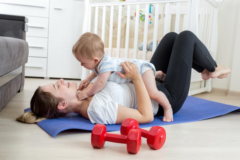 Portrait of happy laughing woman with baby exercising on floor at home. Happy laughing women with baby exercising on floor at home royalty free stock photos