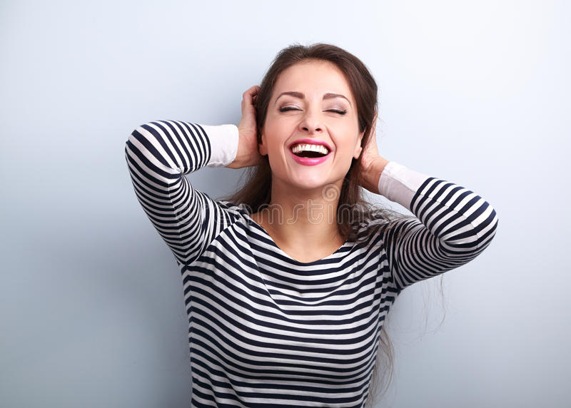 Happy laughing young casual woman with closed eyes holding the h royalty free stock image