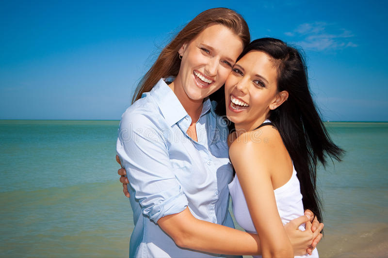 Happy lesbian couple. Gay couple standing at the beach, looking into camera
