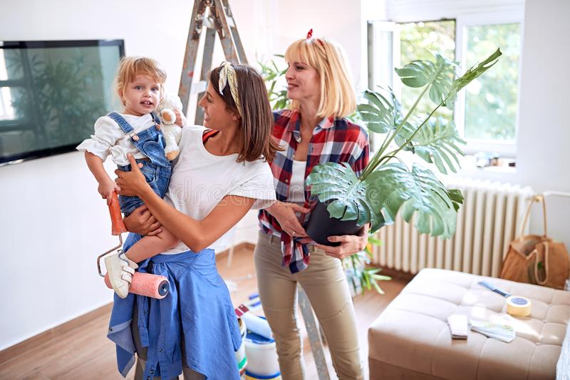 Lesbian couple women moving into new home and having fun with a toddler girl royalty free stock photography