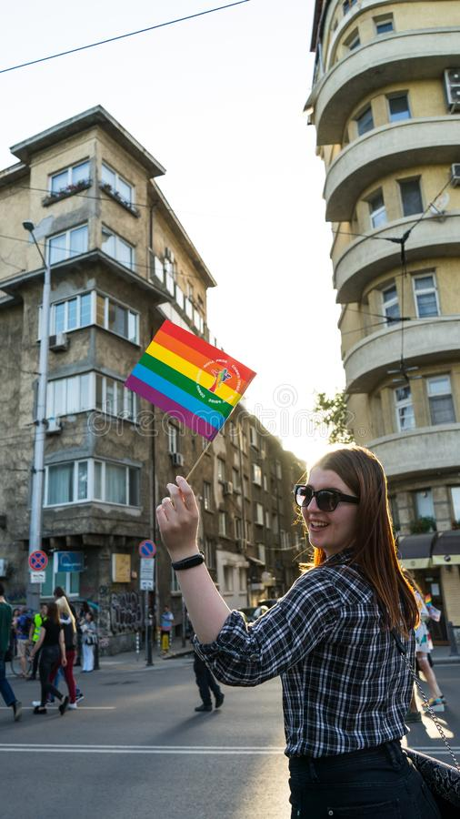 Happy Lesbian woman waving a rainbow flag in a Pride parade, Sofia Pride Festival in the street. Red head sunglasses proud royalty free stock photography