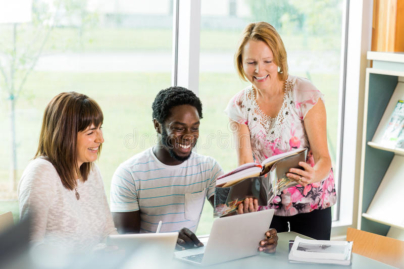 Happy Librarian Assisting Students In Library stock photo