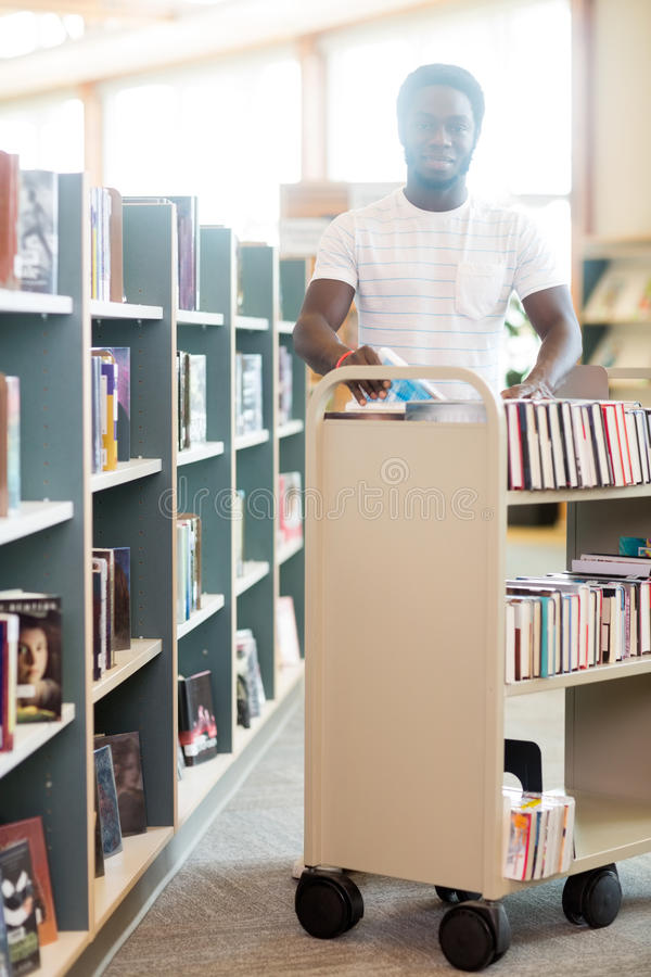 Happy Librarian With Trolley Of Books In Library stock photos