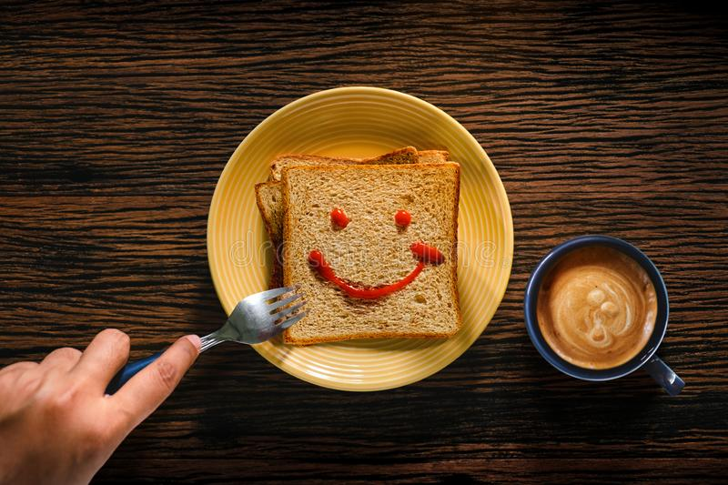Happy Life concept. Young Person Eating Bread and Coffee Cup in Breakfast Time. Smiling Face Drawn on Bread. Top View stock photography