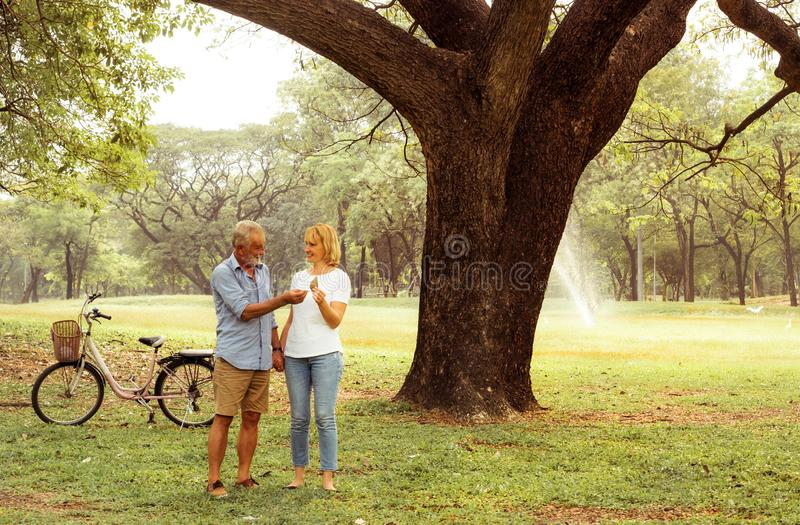 Happy life, family, age, old age, relationship and people concept - senior couple hugging in city park royalty free stock image
