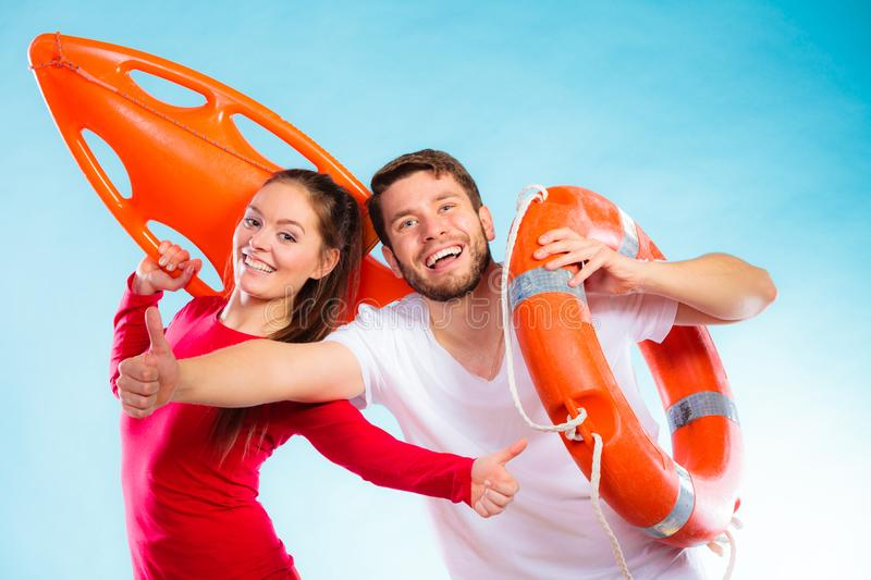 Happy lifeguard couple with equipment. Accident prevention and water rescue. Man and women lifeguard couple holding buoy lifesaver equipment giving thumb ub hand stock photos