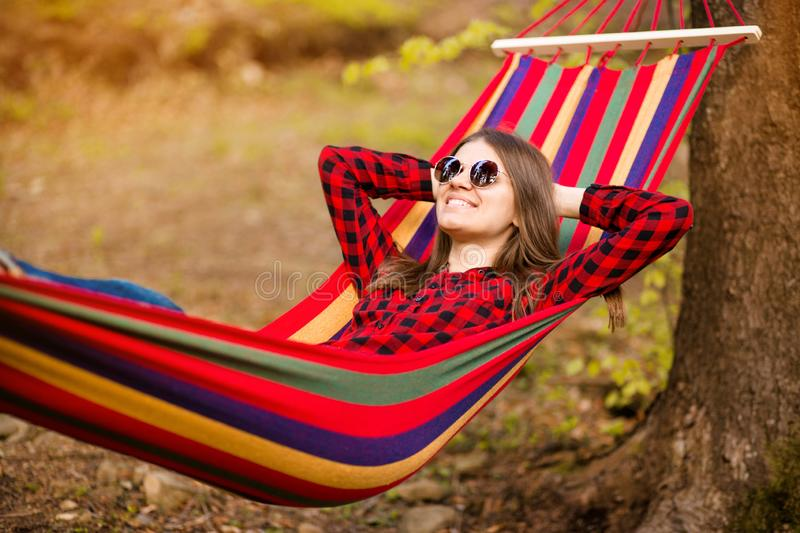 Happy lifestyle concept. Beautiful carefree woman in sunglasses in forest being happy outdoors while rest on hammock royalty free stock image