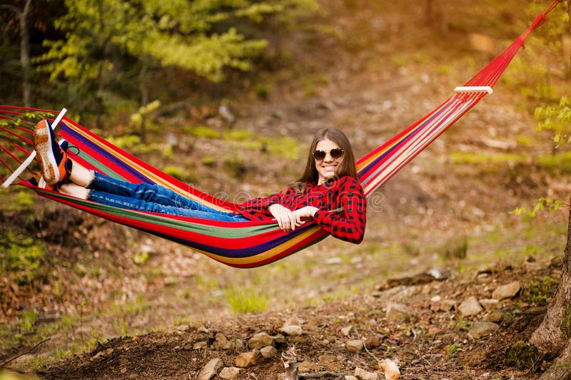 Happy lifestyle concept. Beautiful carefree woman in sunglasses in forest being happy outdoors while rest on hammock stock photography
