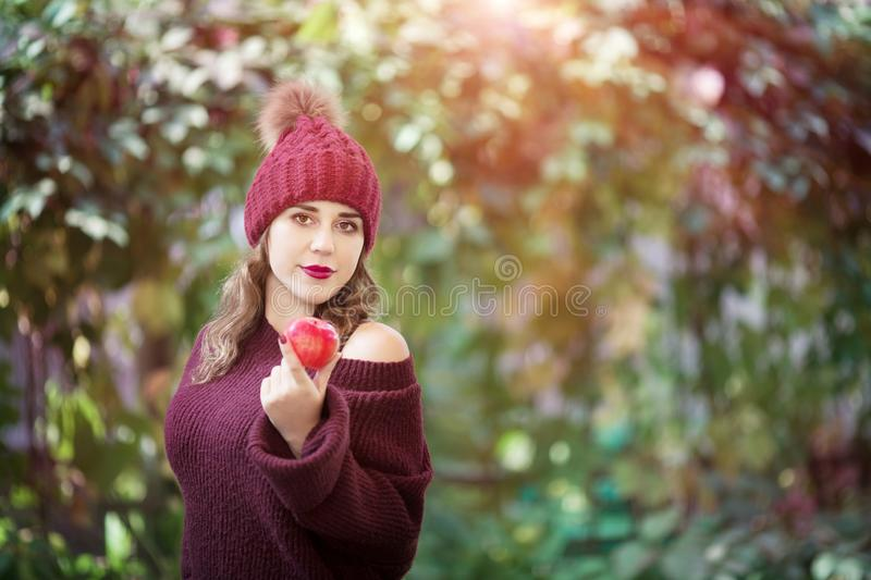 Happy lifestyle portrait of a beautiful young woman in a warm autumn hat with an apple in her hand. royalty free stock photos