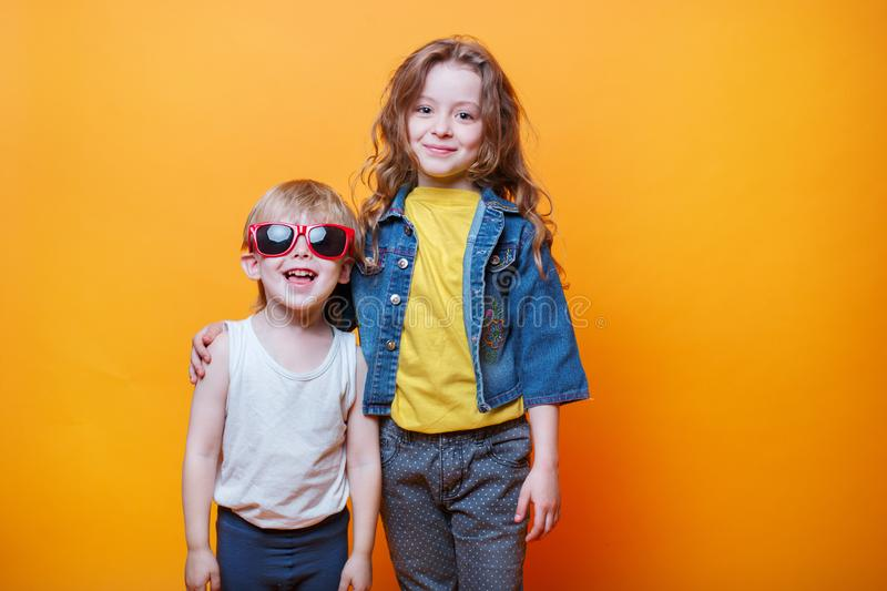 Happy liitle brother and sister on orange background royalty free stock image
