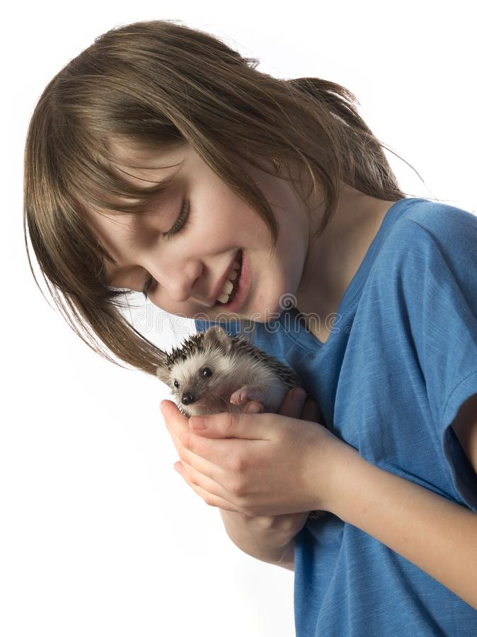 Happy litle girl with her pet African pygmy hedgehog royalty free stock image