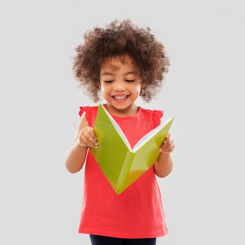Happy little african american girl reading book royalty free stock images