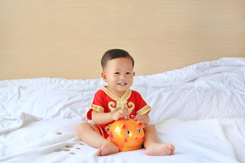 Happy little Asian baby boy in traditional Chinese dress putting some coins into a piggy bank sitting on bed at home. Kid saving. Money concept stock photography