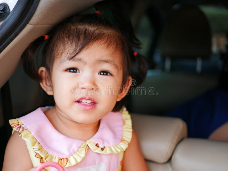Happy little Asian baby girl, 24 months old, enjoys staying in a car boot.  stock images