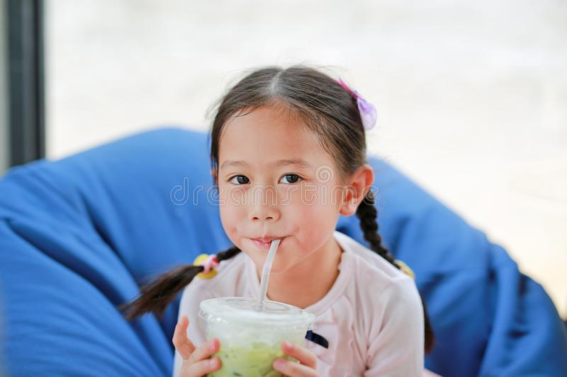 Happy little Asian child girl drinking iced Matcha Green Tea lying on sofa at cafe royalty free stock images