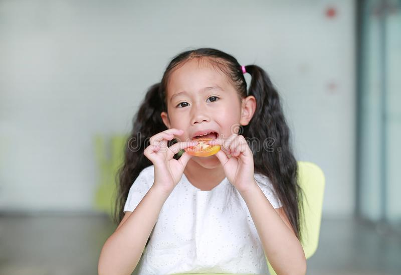 Happy little Asian child girl eating a piece of sliced tomato. Kid eating healthy food concept.  stock images