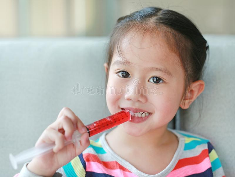 Happy little Asian child girl feeding liquid medicine with a syringe by self.  royalty free stock photography