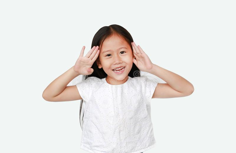 Happy little Asian child girl gestures playing peekaboo over white background. Kid posture open hands from eyes with smile royalty free stock photo