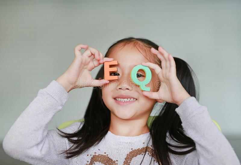 Happy little Asian child girl holding alphabet EQ Emotional Quotient text on her face. Education concept stock photography