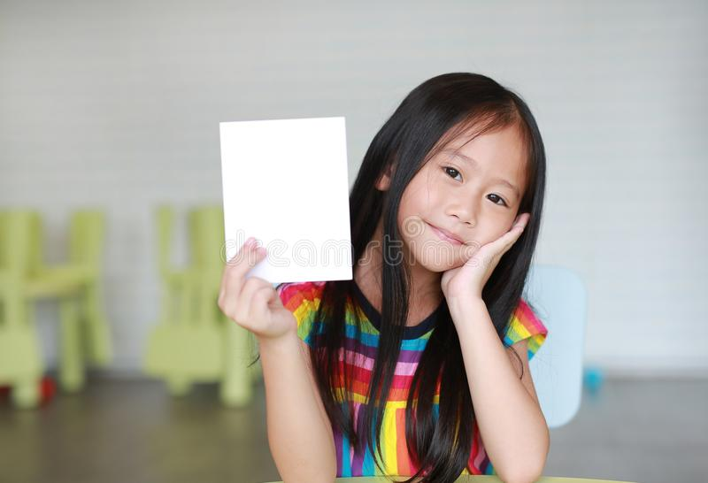 Happy little Asian child girl holding blank white paper card in her hand. Kid showing empty paper note copy space in children room stock image