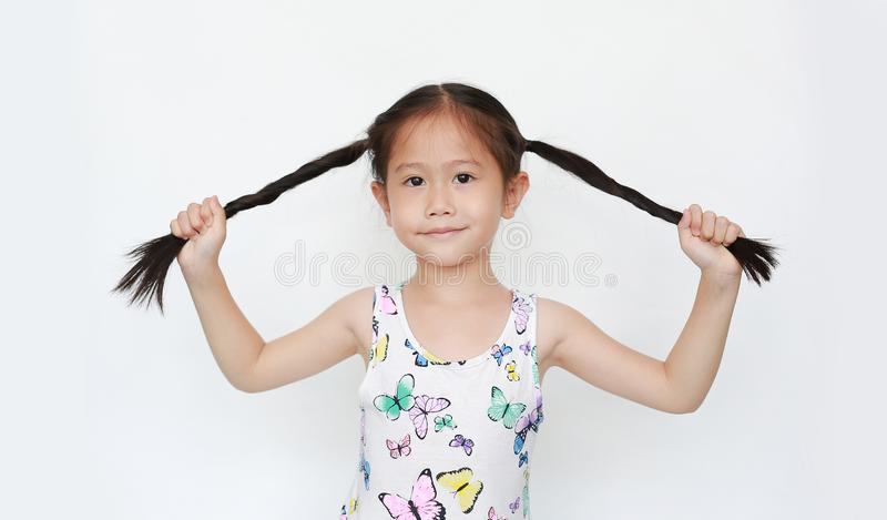 Happy of little Asian child girl holding pigtail on white background. Portrait smiling kid with two pigtails.  stock photo