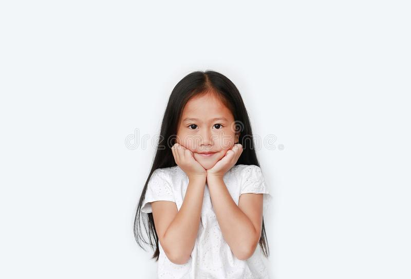 Happy little asian child girl keeps both hands on cheeks over white background with looking at camera. Charming and positive stock images