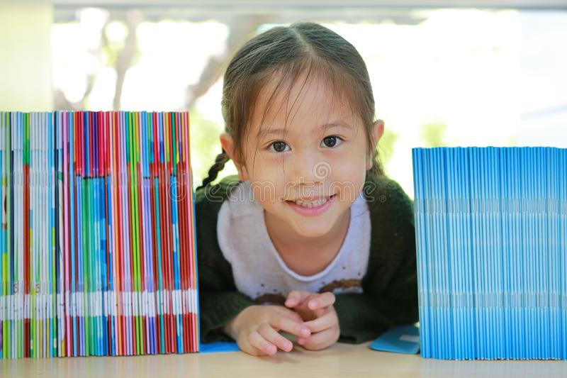 Happy little Asian child girl lying on bookshelf at library. Children creativity and imagination concept.  royalty free stock photography